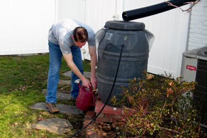 Man filling up a watering can from a rain barrel.