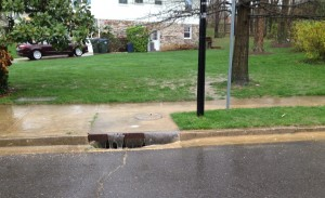 Heavy rain flows off of sidewalk and off of street and into a storm drain.