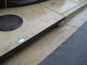 Rain flows down curb and gutter and into a storm drain.