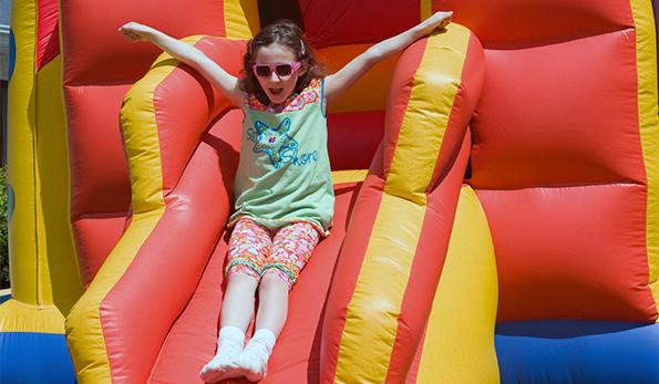 girl going down moonbounce slide