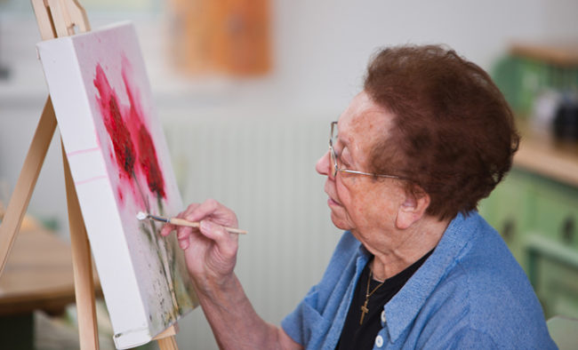 Older woman paints a picture