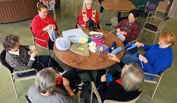 seniors doing crafts around a circular table