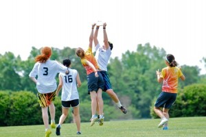 Players jumping for ultimate frisbee