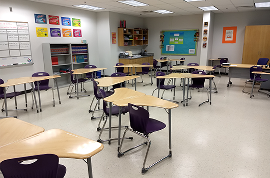 classroom with desks and decorations hanging on walls