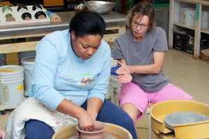 One woman molds a clay pot while another woman gives instructions.