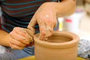 Woman making a ceramic pot out of clay.
