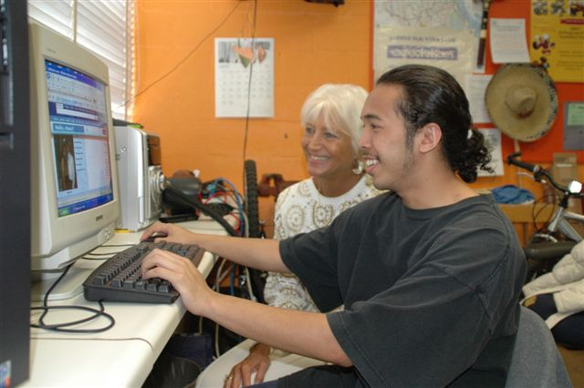 senior and teen with computer
