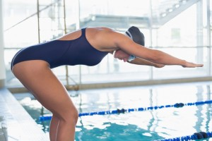 Side view of a fit female swimmer about to dive into the pool at leisure center