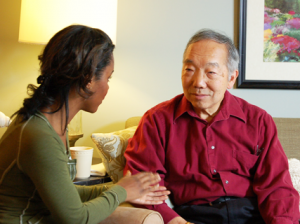 Woman speaking with older Asian man