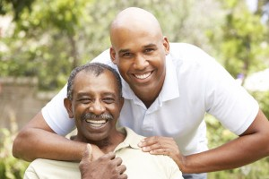 Older African American man with son or caregiver
