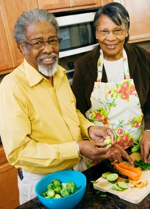 African American older couple cooking together