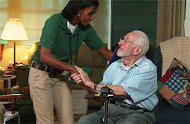 Older Man in Wheelchair Receiving Assistance from Aide
