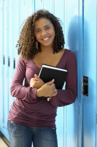 Teenage girl with books at school