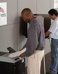 Voter inserting paper ballot into scanner