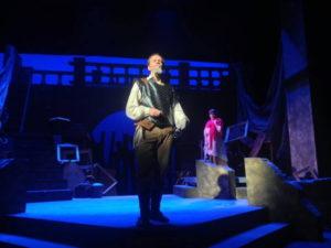 man on stage singing under spotlight