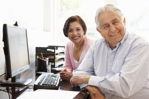 Smiling couple sitting in front of a computer