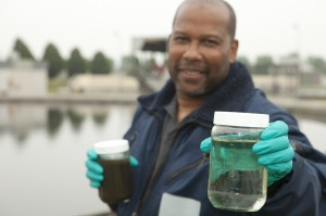 Man working at a water treatment plant, holding water sample in hands.