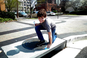 Jefferson Middle School student affixing storm drain marker.